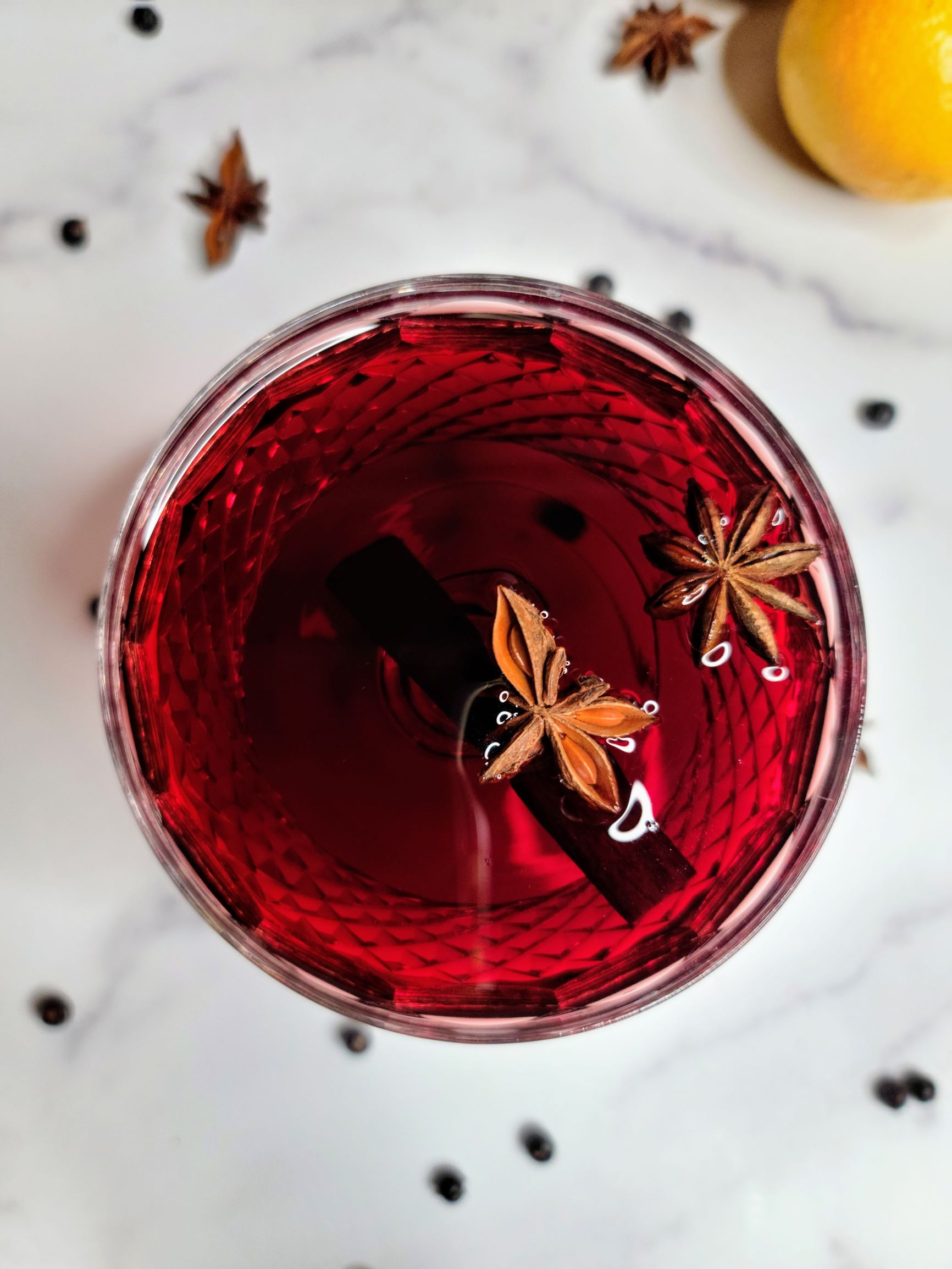 Spiced mulled wine in glass, with cinnamon sticks and star anise.
