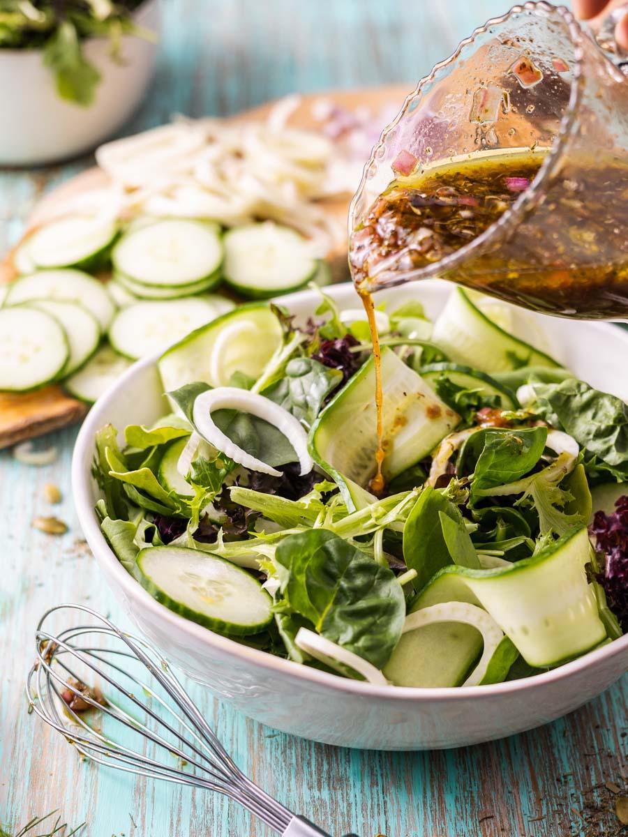 pouring blackcurrant vinaigrette onto a salad