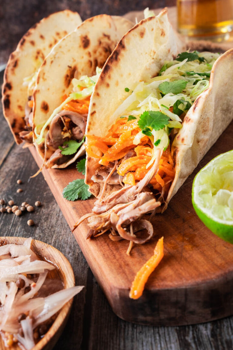 Lamb Tacos with Pickled Shallots, Cabbage Slaw, and Carrot Salad on wooden board.