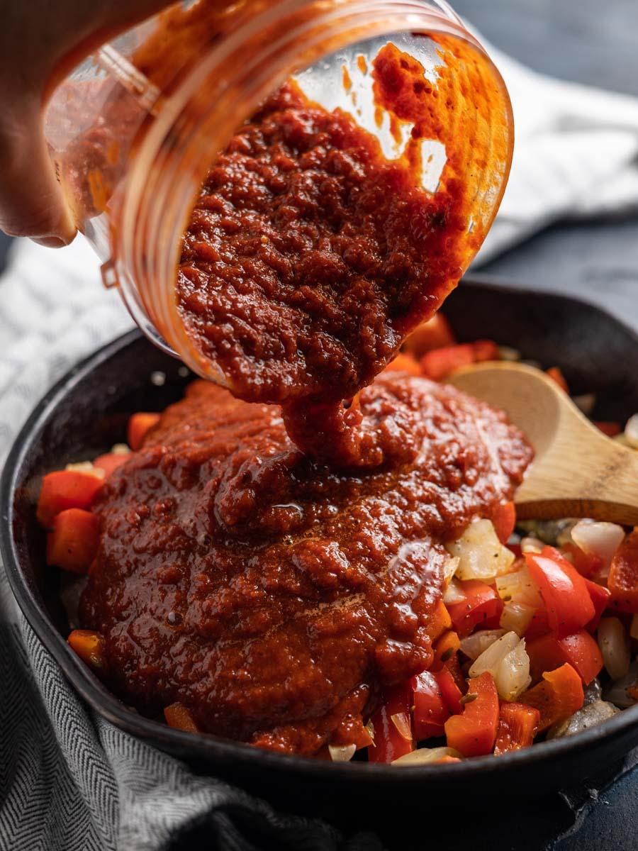 pouring adobo into a castiron pan