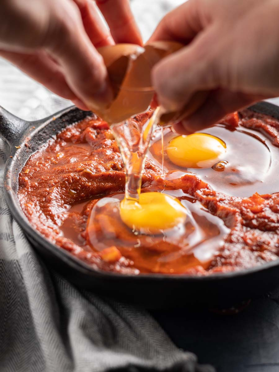breaking eggs into the castiron pan filled