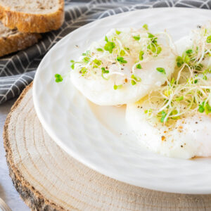Thumbnail of poached eggs with watercress on top on wooden slab..