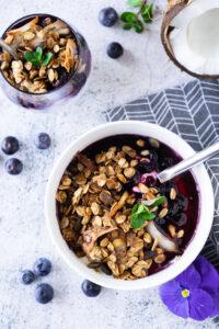 vanilla yogurt, granola, and blueberry compote in a bowl