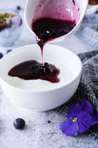 Blueberry compote poured over yogurt.