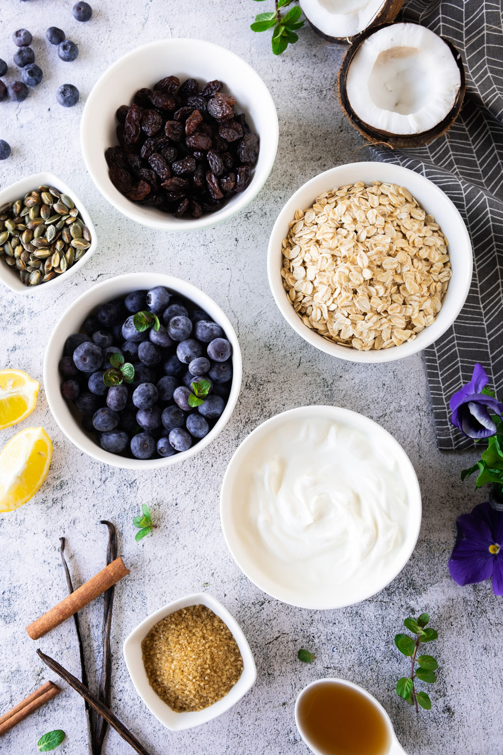 Vanilla yogurt with blueberry compote and granola ingredients.