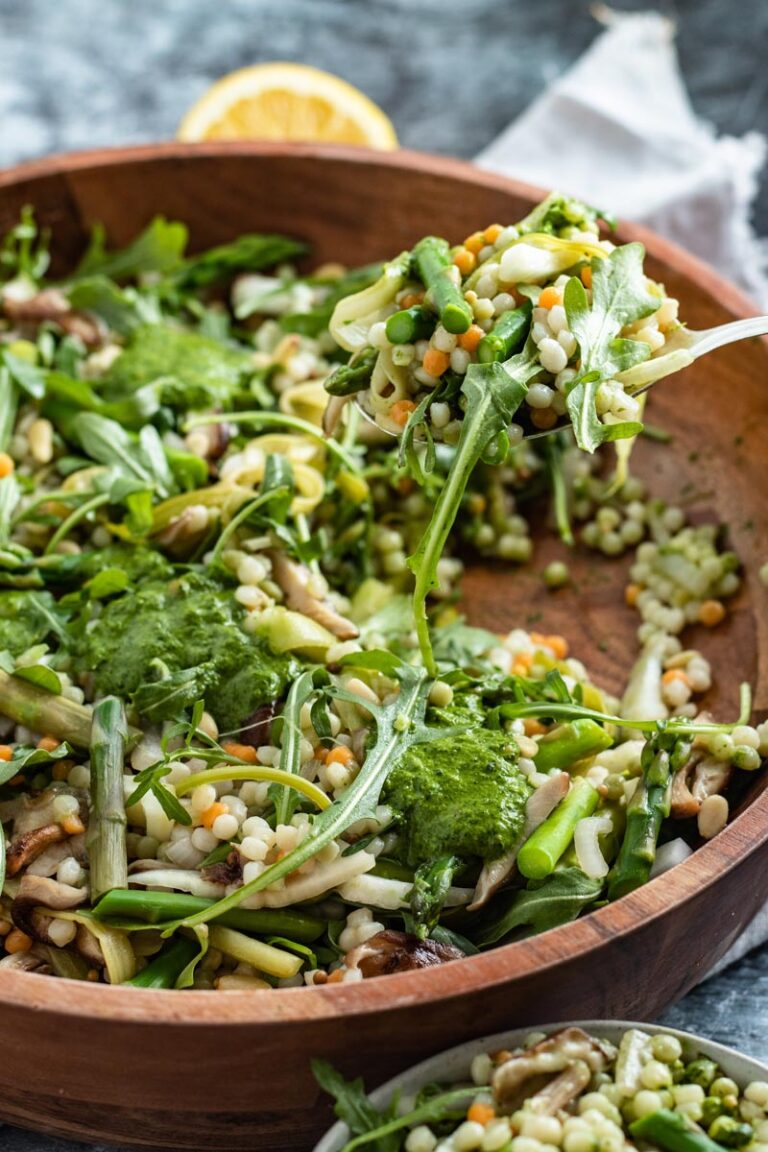 mushroom asparagus couscous salad in bowl with serving spoon