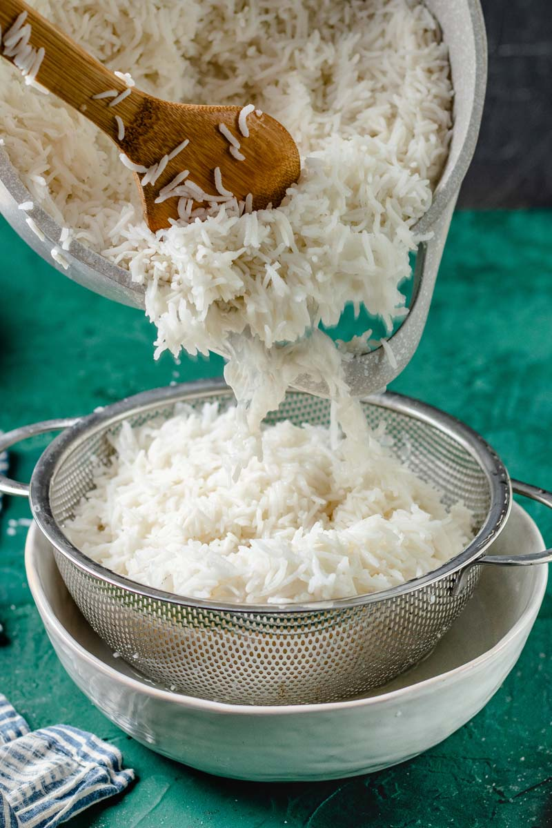 Straining cooked rice into a sieve