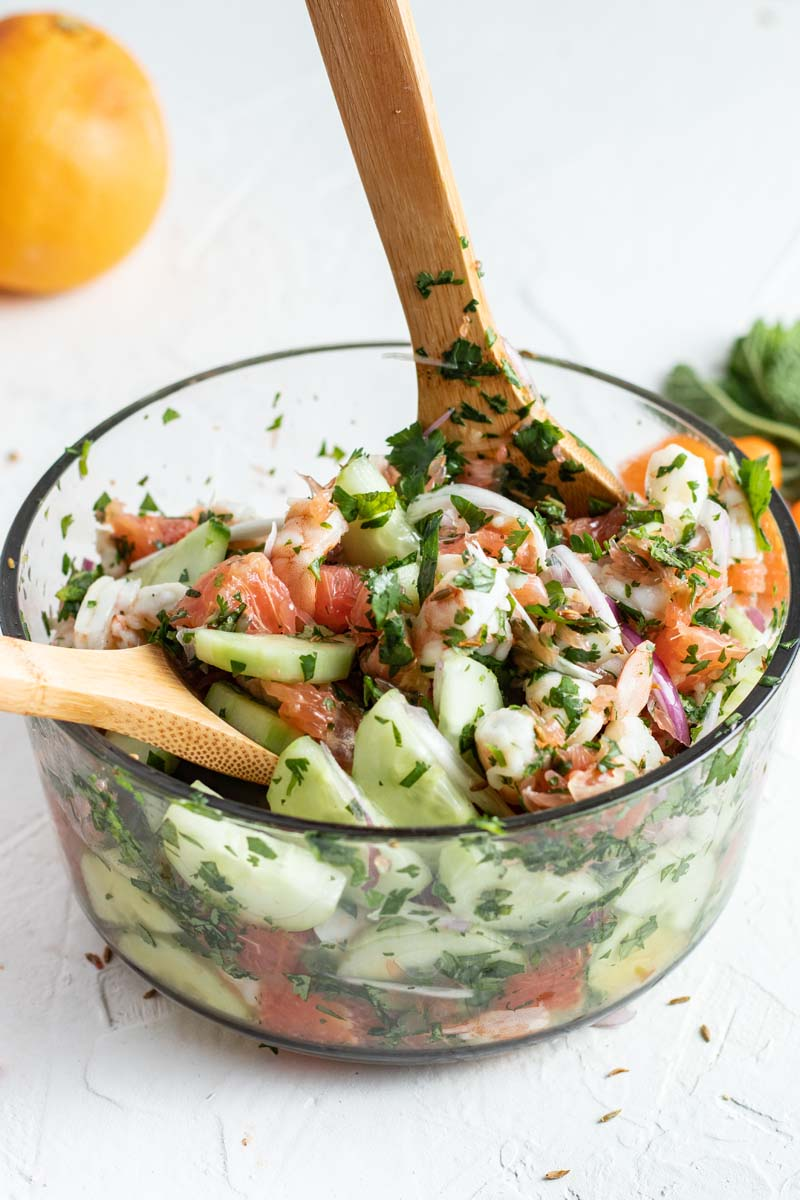 tossing shrimp ceviche in a bowl