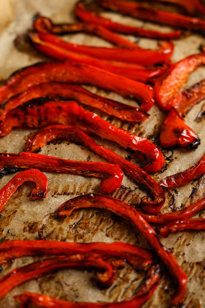 Roasted red peppers on a baking sheet after baking