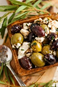 marinated greek olives and feta cheese in a dish